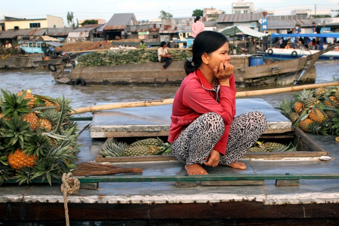 A pineapple vendor sits on her boat at a floating market in the Mekong Delta.